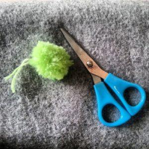 Sådan laver du en pompom - Klip siderne på det opsnoede garn, og puf lidt op i pompom'en så den rigtigt strutter.